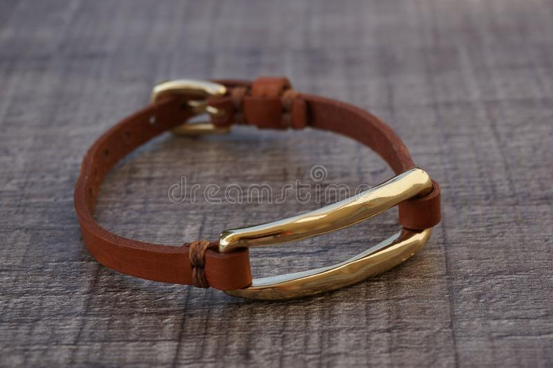 Brown leather bracelet gold plated. Alicante, Spain - June, 2019: Uno de 50 & x28;One of 50& x29; brand thin light brown leather  bracelet with gold plated shine royalty free stock image