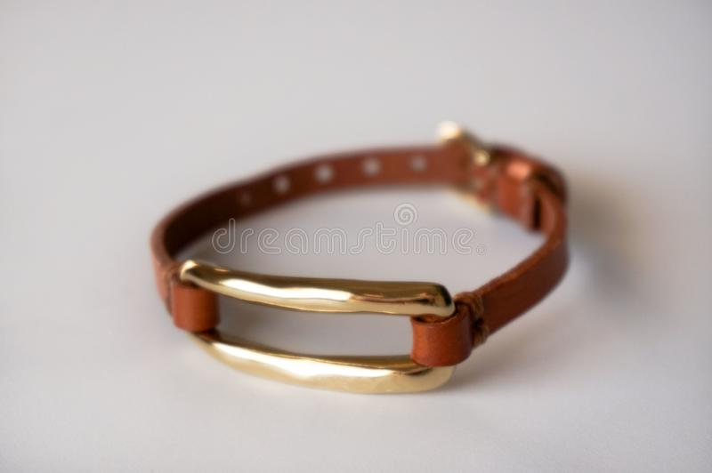 Brown leather bracelet gold plated. Alicante, Spain - June, 2019: Uno de 50 & x28;One of 50& x29; brand thin light brown leather  bracelet with gold plated shine royalty free stock photos