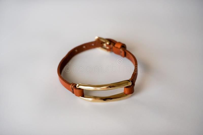 Brown leather bracelet gold plated. Alicante, Spain - June, 2019: Uno de 50 & x28;One of 50& x29; brand thin light brown leather  bracelet with gold plated shine stock photography