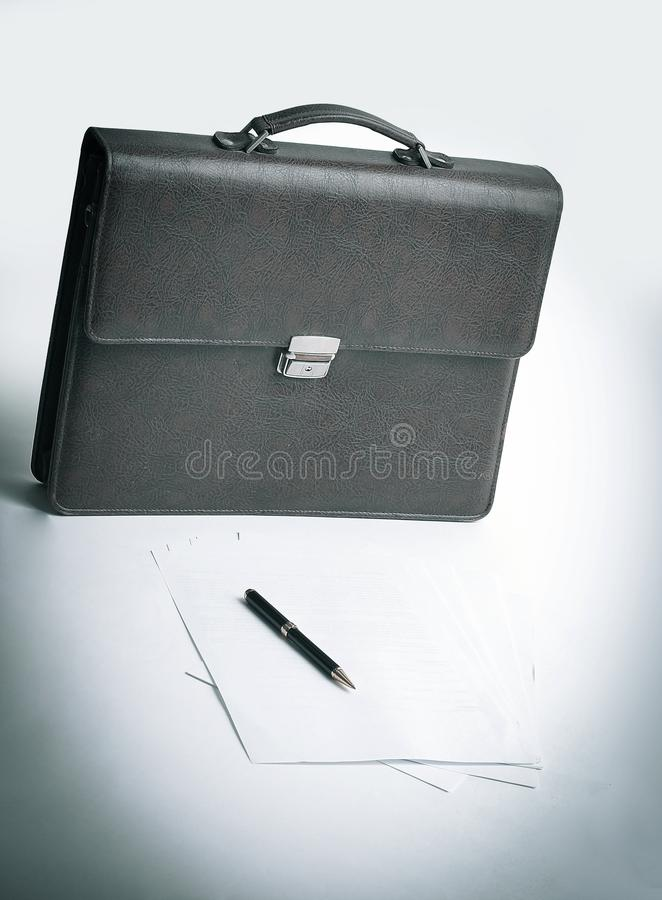 Brown leather briefcase of a businessman and a handle in the wor royalty free stock photo