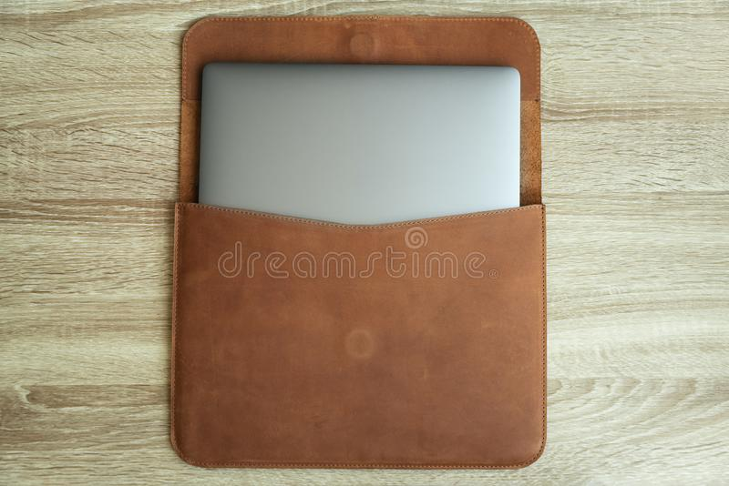 Brown leather case with laptop on wooden table. Top view. Copy space.  royalty free stock image