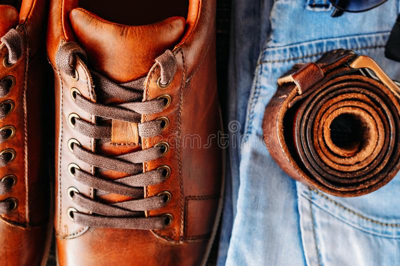 Brown leather casual shoes, jeans and belt top view close up. Fashion concept. Close up of brown leather casual shoes; jeans and belt top view. Fashion concept stock photography