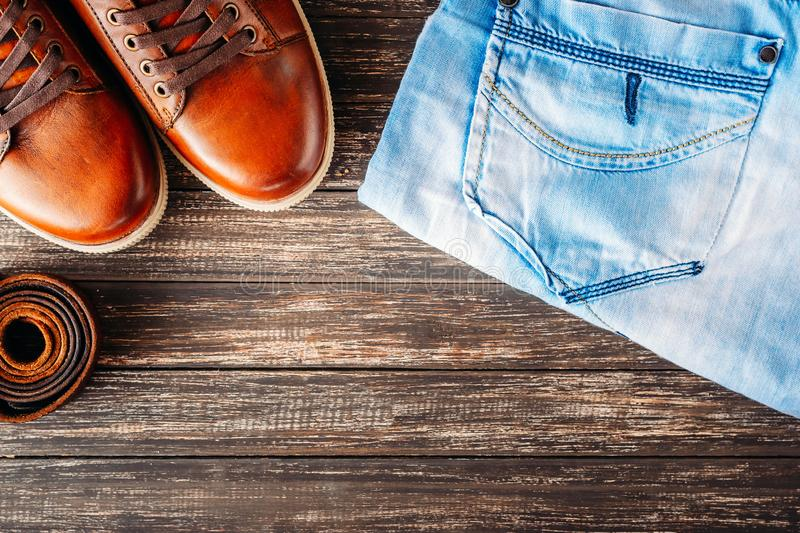 Brown leather men`s boots, belt and blue jeans on a dark wooden background, top view with copy space. Brown leather men`s boots, belt and blue jeans on dark royalty free stock images