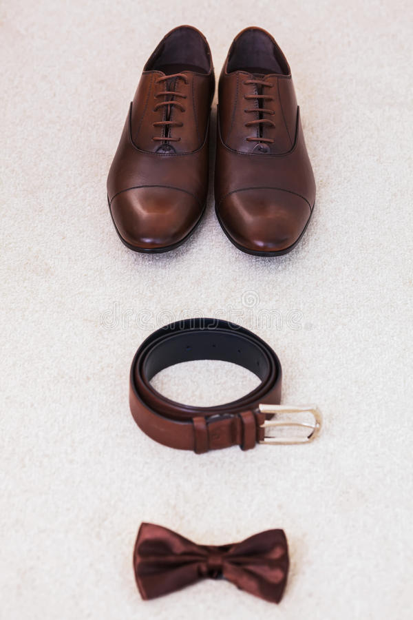 Brown leather men`s shoes with belt, bow-tie. Set groom accessories. Top view stock photography