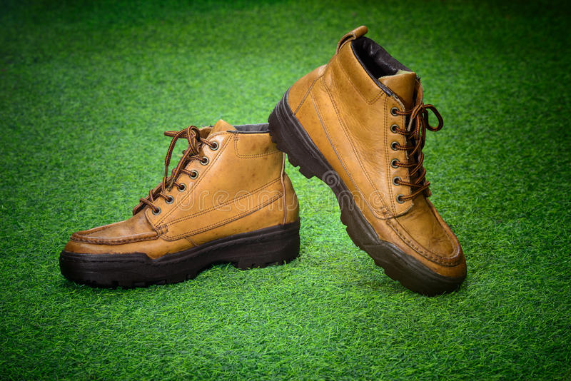 Brown leather retro shoes as for adventure shoes` style on green royalty free stock photos