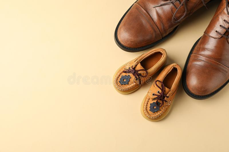 Brown leather shoes and children`s shoes on color background, space for text stock photos