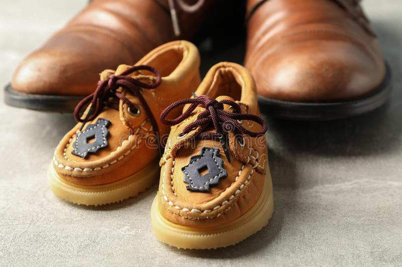 Brown leather shoes and children`s shoes on grey background, space for text royalty free stock photo