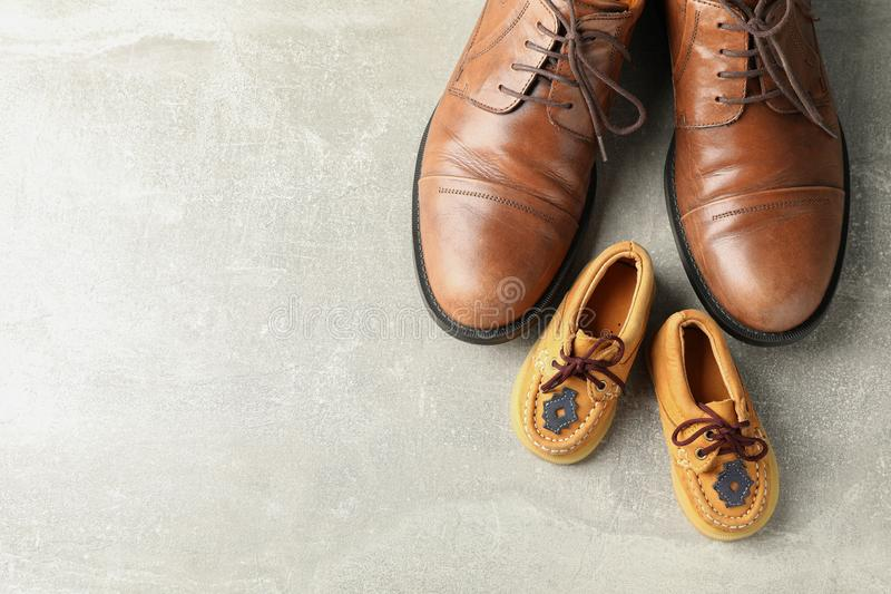 Brown leather shoes and children`s shoes on grey background, space for text royalty free stock photography