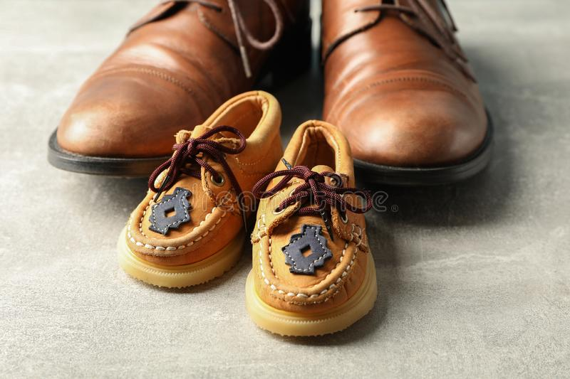 Brown leather shoes and children`s shoes on grey background, space for text stock photos