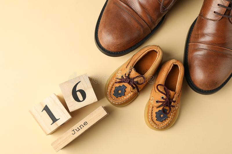 Brown leather shoes, children`s shoes and wooden calendar on color background, space for text. And top view stock photography
