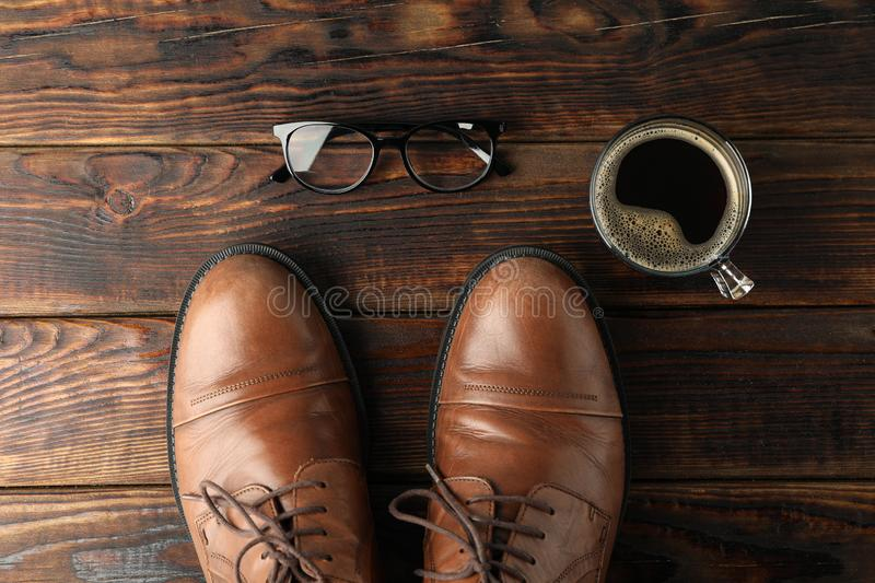 Brown leather shoes, cup of coffee and glasses on wooden background, space for text stock photo
