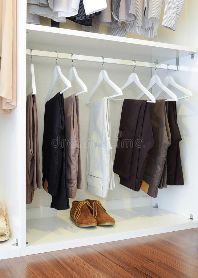 Brown leather shoes and row of black pants hangs in wardrobe. At home royalty free stock image