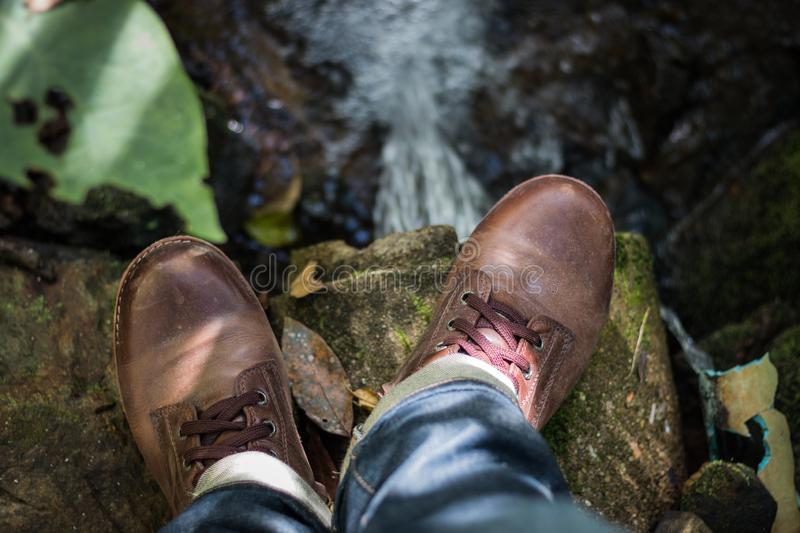 Brown Leather Shoes. Stomping on rocks The bottom of the rock is a waterfall stock image