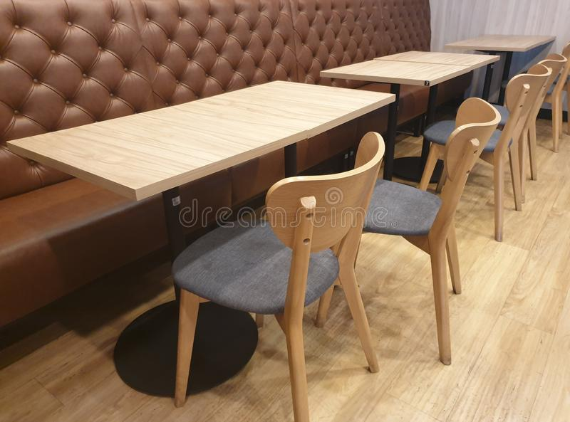 Brown leather sofa and wooden chair with square table. In the empty restaurant royalty free stock photo