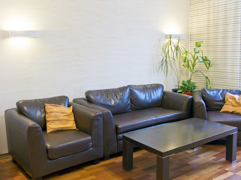Brown leather sofas. Modern home interior with elegant brown leather sofas and armchairs royalty free stock image
