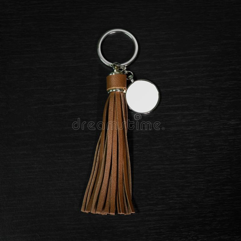 Brown Leather Tassel key ring on black wooden background. Fashion leather key chain for decoration. Brown Leather Tassel key ring on black wooden background royalty free stock image