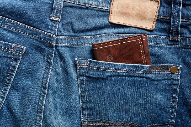 Brown leather wallet in the back pocket of a blue jean stock photo