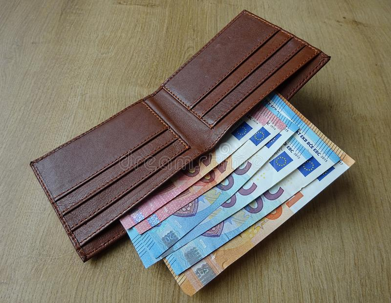 Brown leather wallet with Euro European paper money banknotes stock image