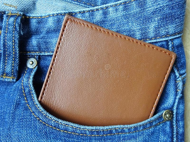 Brown leather wallet inside the jeans pocket stock image