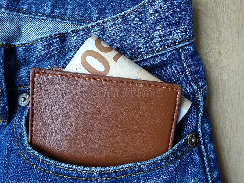 Brown leather wallet and money inside the jeans pocket stock photos