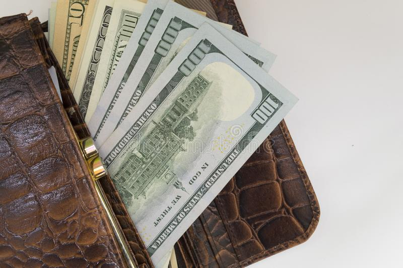 A brown leather wallet from which one hundred dollar bills peep out, and various denominations stock image
