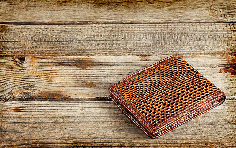 Brown leather wallet. On a wooden background royalty free stock photography