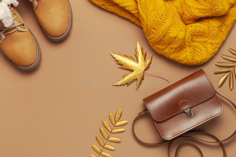 Brown leather women bag, orange knitted sweater, warm boots, golden autumn leaf on brown background top view flat lay. Fashionable stock photo