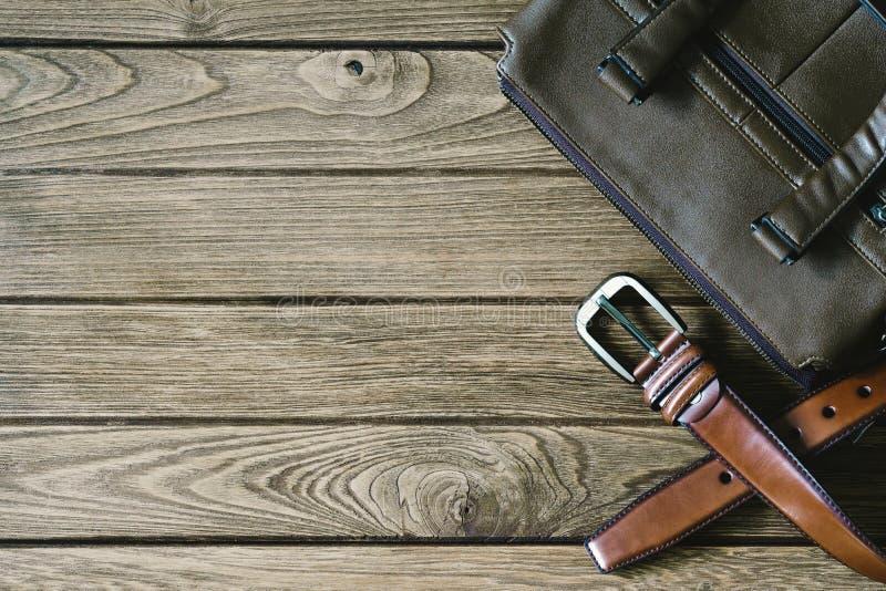 Brown-Ledergürtel und Tasche auf dem Holztisch, Draufsicht mit c lizenzfreie stockbilder