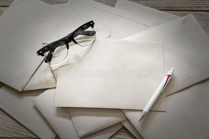 Brown Letter Envelop with glasses and pen on wooden table.  royalty free stock photography