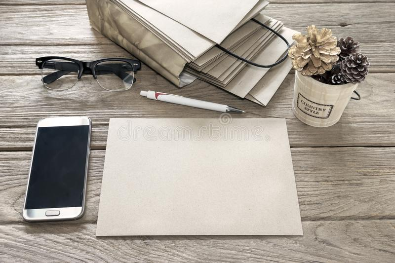 Brown Letter Envelop with pen,bucket,smartphone,bag,glasses on wooden table.  royalty free stock photography