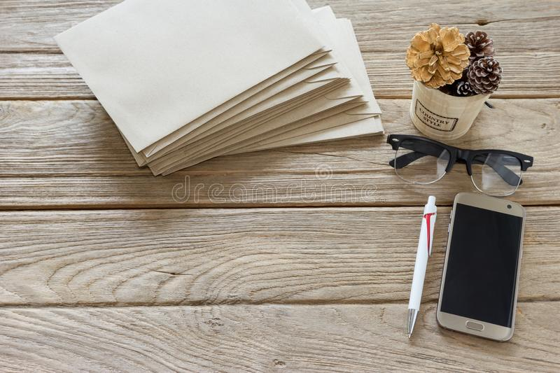 Brown Letter Envelop with pen,bucket,smartphone,glasses on wooden table.  royalty free stock photos