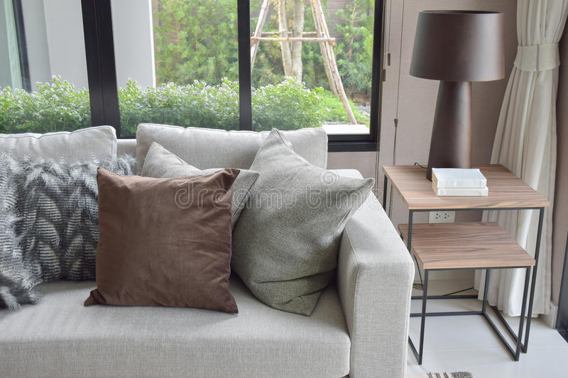 Brown and light gray pillows setting on beige couch in living room stock images