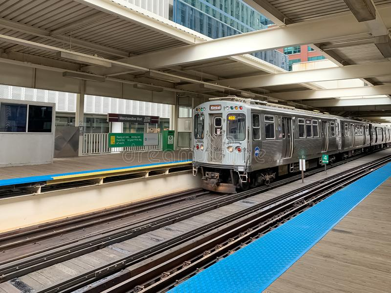 Brown line el train moving into Merchandise Mart station where the platform is empty at midday. Chicago, IL / USA - 7/26/19: Brown line el train moving into stock images