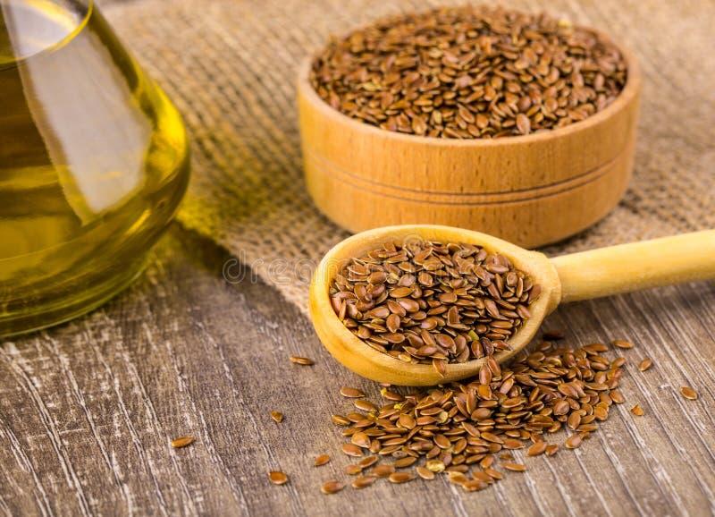 Brown lna ziarna i flaxseed olej na drewnianej powierzchni obraz stock