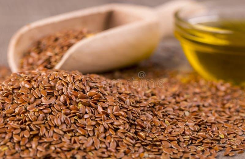 Brown lna ziarna i flaxseed olej na drewnianym stole obrazy stock
