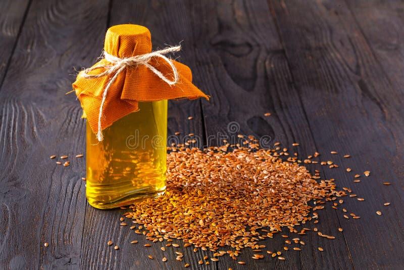 Brown lna ziarna w łyżki i flaxseed oleju w szklanej butelce na białym drewnianym tle Lna olej jest bogaty w omega-3 tłustym kwas zdjęcie royalty free