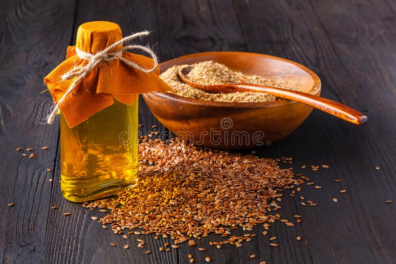 Brown lna ziarna w łyżki i flaxseed oleju w szklanej butelce na białym drewnianym tle Lna olej jest bogaty w omega-3 tłustym kwas obrazy stock