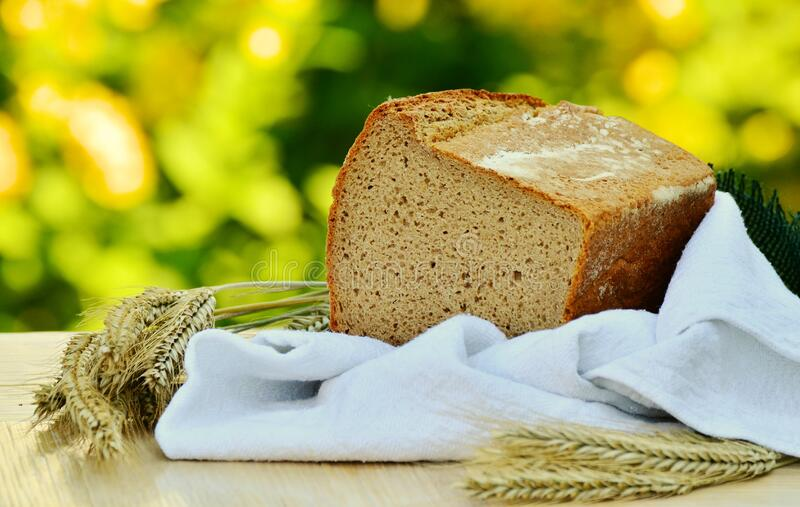 Brown Loft Bread in White Textile on Beige Table royalty free stock photos