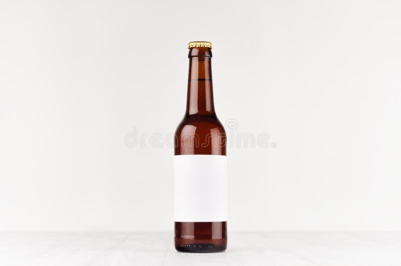 Brown longneck piwna butelka 330ml z pustą białą etykietką na białej drewnianej desce, wyśmiewa up zdjęcie royalty free
