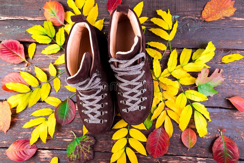 Brown mężczyzna zamszowy inicjuje na drewnianym tle z liśćmi Mieszkanie nieatutowy Jesieni lub zimy buty obraz stock