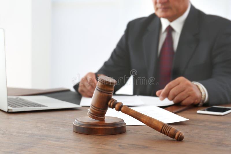 Brown młoteczek na drewnianym stołu i samiec prawniku na tle, zamyka up zdjęcie royalty free