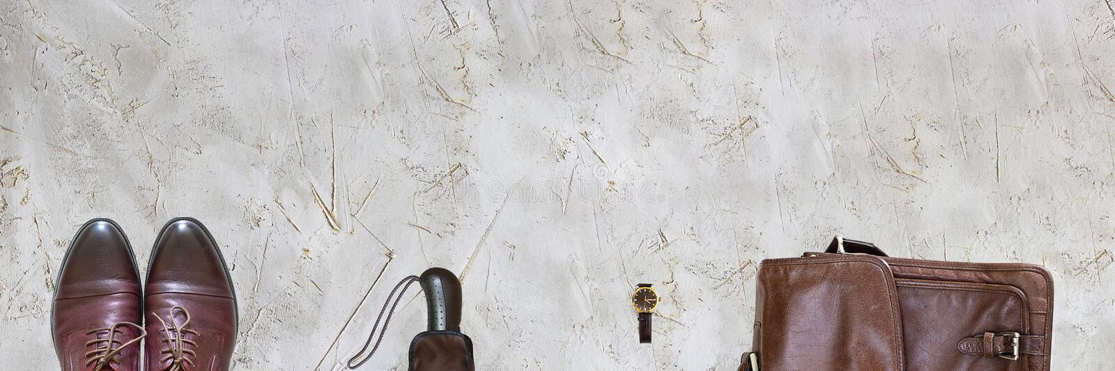 Brown man Accessories classic shoes, umbrella, watches, leather bag on grey textured cement rough surface. Long horizontal banner stock photography
