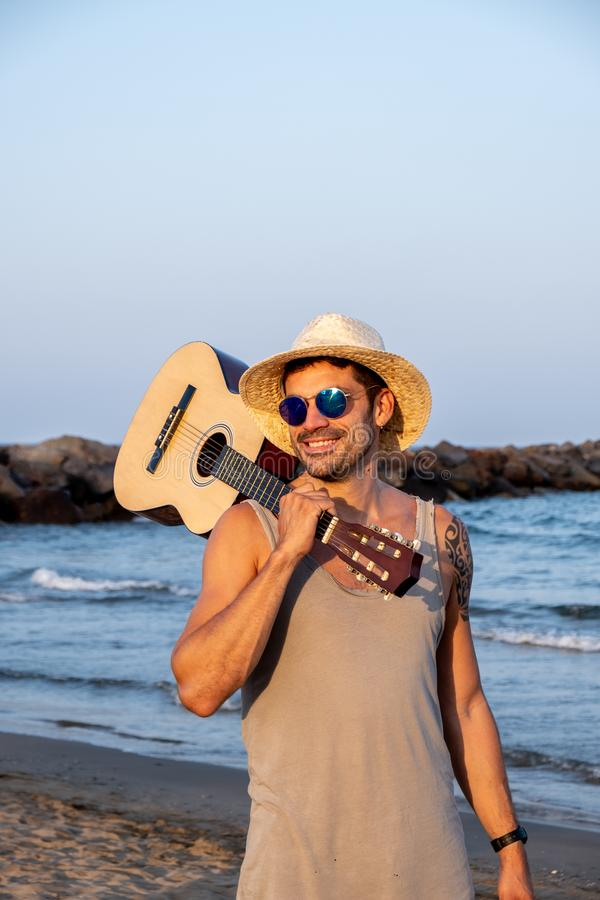 Brown man dressed in summer form posing on the beach with a Spanish guitar stock photos