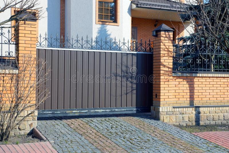 Brown metal gates and brick fence on the street near the sidewalk. Brown metal gate and brick fence in the street by the sidewalk royalty free stock images