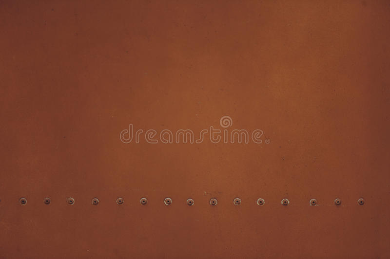 Brown metal plate with rivets for grunge or abstract background. royalty free stock photo