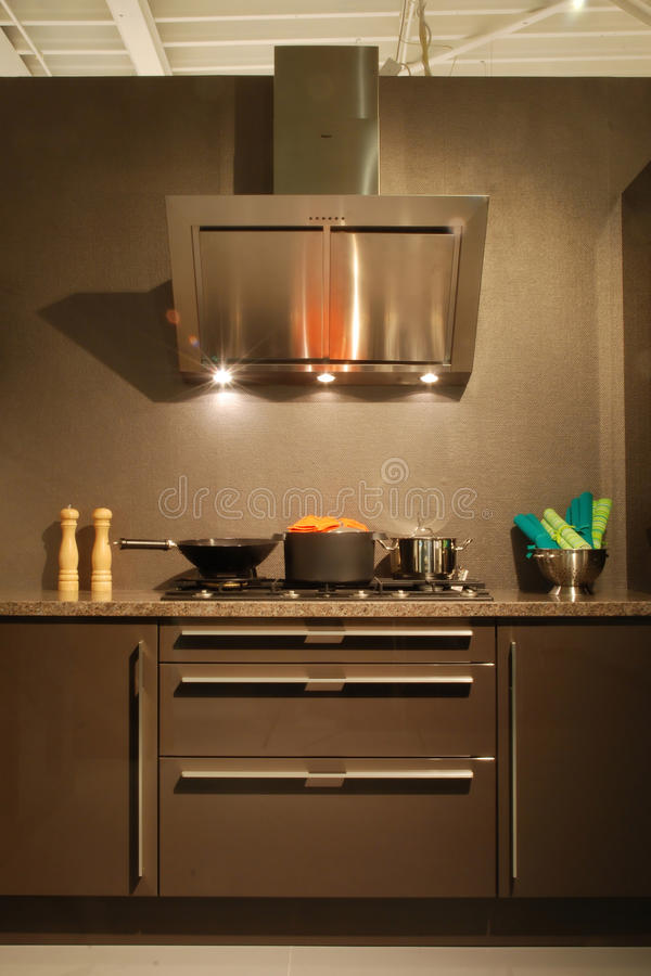 Brown modern gloss kitchen - detail cooking area. Brown modern design gloss kitchen / detail cooking area with extractor hood and pans stock photo