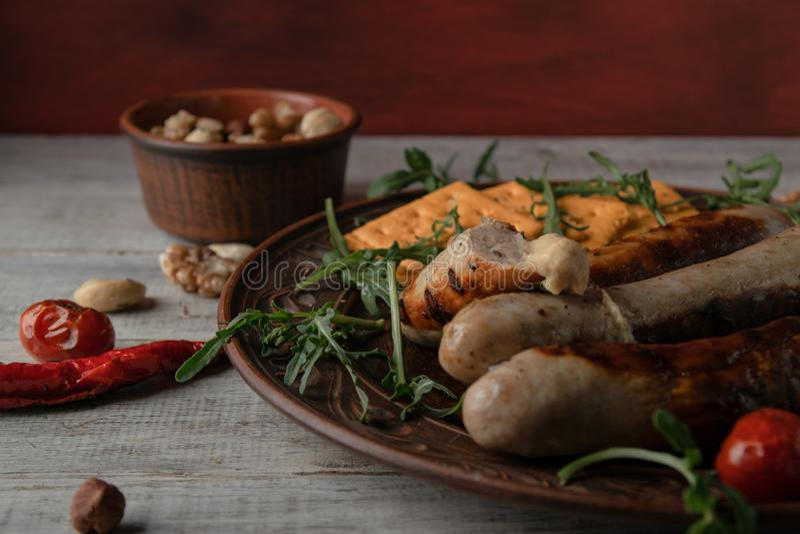 Brown naczynie z piec na grillu kiełbasami z musztardą i arugula zdjęcia stock