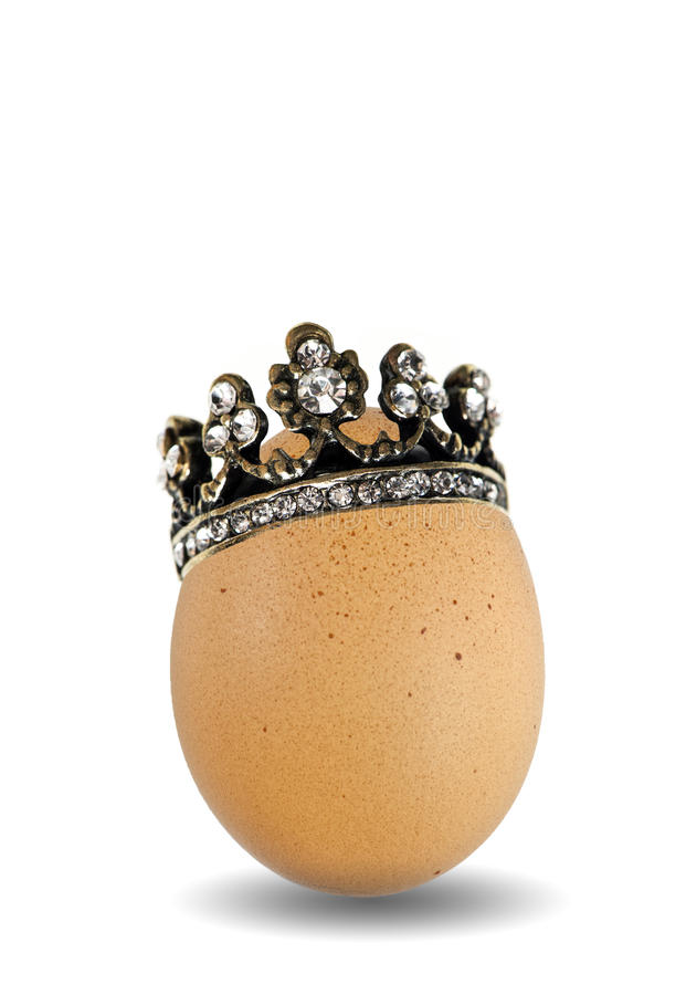Brown natural easter egg with golden crown royalty free stock photography