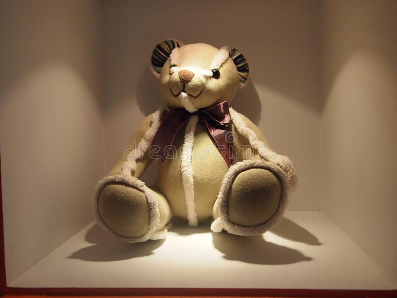 Brown niedźwiedź i biel koronka znosimy lalę, siedzi cicho na pokazu stojaku lekki jaśnienie na niedźwiedziu obraz stock