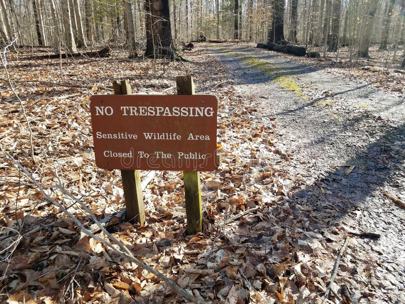 Brown no trespassing sensitive wildlife area closed to the public sign. And trail royalty free stock photography